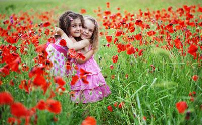 Two girls in a friendship hug in field of flowers.