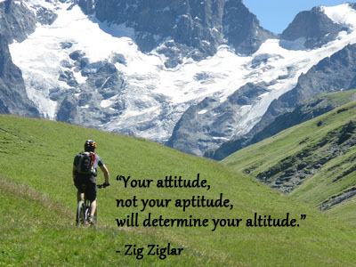 Mountain biking in snow capped mountains with Zig Ziglar quote about attitude.